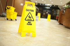 Caution lobby mop bucket and sign stock images