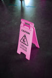 Caution pink sign for warning, falling in love, on a floor. Caution pink plastic sign for warning, with text falling in love, on a floor stock photo