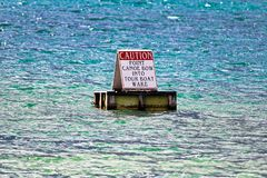 Caution point canoe bow into tour boat wake sign royalty free stock photography