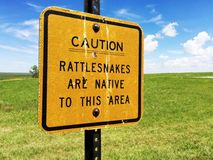 A caution rattlesnakes are native sign. A caution rattlesnakes are native to this area. The sign is covered in bird poop Royalty Free Stock Photo