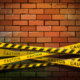 Caution ribbon on brick wall Royalty Free Stock Photography