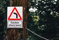 A `Caution Sharp Bend` sign hung up on a tree in the UK in a forest. 2018 royalty free stock photo