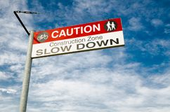 Caution Sign for a Bicycle rider to slow down in the construction area. A Caution Sign for a Bicycle rider to slow down in the construction area stock photo