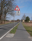Caution sign in countryside. Traffic sign on road warning about children rollerskating on sidewalk in countryside Royalty Free Stock Photo