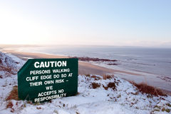 Caution sign on hazardous cliff edge Stock Photo
