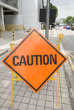 Caution sign. Orange Caution sign on the road Royalty Free Stock Photography