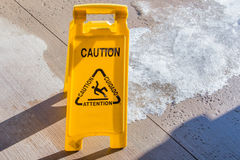 Caution sign. Yellow caution sign outside on an icy hotel patio Stock Photography