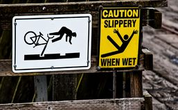 2 caution signs on a wooden rail Stock Photo