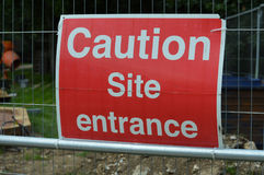 Caution site entrance sign. Fence mounted construction site caution sign stock photo