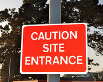 Caution site entrance. A caution site entrance sign on a pole Royalty Free Stock Photography