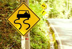 Caution of slippery roads - traffic signs beside country road Royalty Free Stock Photo