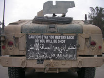 CAUTION STAY 100 METERS BACK OR YOU WILL BE SHOT. Warning signs posted on the back of MNFI USA vehicles till 2007  IRAQ war Royalty Free Stock Photos