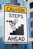 Caution Steps Ahead. Caution sign that dramatically depicts a bicyclist falling headfirst down a steep staircase Royalty Free Stock Image
