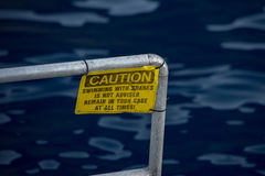 Caution swiimming with sharks yellow sign Stock Images