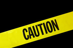Caution tape. Yellow caution tape on black background stock image
