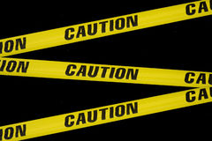 Caution tape. Criss crossing caution tape on a black background royalty free stock images