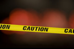 Caution tape. Over a black background with flashing lights in the background stock photography