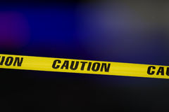 Caution tape. Over a black background with flashing lights in the background stock images