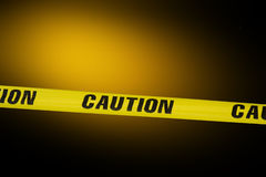 Caution tape. Over a black background with flashing lights in the background royalty free stock photo