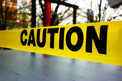 Caution tape. Caution text on yellow warning tape Stock Photography