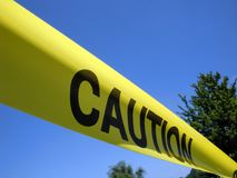 Caution Tape. Bright yellow caution tape stretched against a blue sky stock images