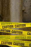 Caution Tape. Crisscrossing in front of a concrete stone wall Royalty Free Stock Images