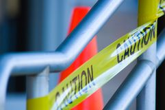 Caution tape with orange traffic cone. Yellow caution tape on stair rail with orange traffic cone behind, very shallow depth of field stock photo