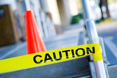 Caution tape with orange traffic cone Stock Photos