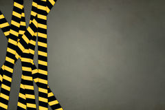 Caution Tape Strips. Yellow and black striped caution bands, on grey background Royalty Free Stock Image