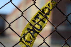 Caution Tape on Fence. Caution tape tied to a chain link fence stock images