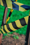 Caution tape / Warning tape. Yellow and black caution / warning tape around rusty metal posts, green grass / lawn on the background. Watch out Royalty Free Stock Photography