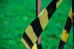 Caution tape / Warning tape. Yellow and black caution / warning tape, green grass / lawn on the background. Watch out Royalty Free Stock Image