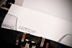 Caution text typed on old black typwriter Royalty Free Stock Image