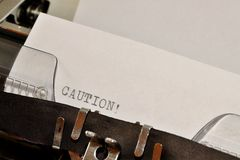 Caution text typed on old black typwriter Royalty Free Stock Photos