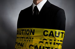 Caution Tie. Image of a suit- wearing man with caution tape wrapped around him Royalty Free Stock Photography