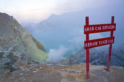 Caution to beware toxic gas at Kawah Ijen volcano spewing out sulphur smoke in the morning. Royalty Free Stock Images
