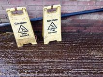 Caution trip hazard plastic signs. Caution trip hazard plastic floor signs stand open on the icy wet cement ground against a plastic sewage pipe and red brick royalty free stock images