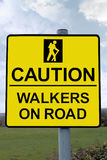 Caution walkers on road sign with clipping path. Warning sign for drivers to be careful of tourists walking on country roads with clipping path Stock Photos