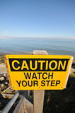 Caution Watch Your Step sign by the ocean Stock Photos