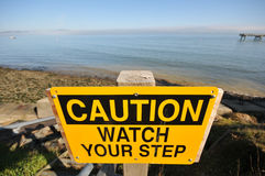 Caution Watch Your Step sign by the ocean Royalty Free Stock Image