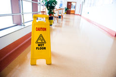 Caution wet floor. Freshly mopped hallway with a caution sign in English Stock Image