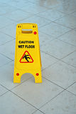 Caution wet floor. Sign stand on a ceramic surface Royalty Free Stock Photography