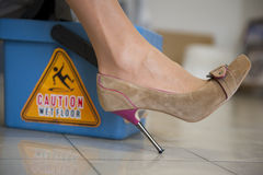 Caution Wet Floor. Woman in sexy High Heel Shoe is slipping on on mopped tiles. The danger sign on the bucket 'caution wet floor' is reflecting on the surface of Stock Images