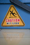 Caution Wet Floor. Danger sign 'Caution Wet Floor' on a blue bucket is reflecting on the wet floor Royalty Free Stock Images