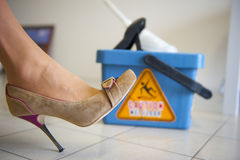 Caution Wet Floor. Woman in sexy High Heel Shoe is slipping on on mopped tiles. The danger sign on the bucket 'caution wet floor' is reflecting on the surface of Stock Photo
