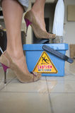 Caution Wet Floor. Cleaner in sexy High Heel Shoe on bucket with water is mopping the tiles. The danger sign on the bucket 'caution wet floor' is reflecting on Royalty Free Stock Photos