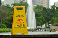 Caution wet floor outside. Sign indicating caution wet floor, outside near fountain Royalty Free Stock Photo