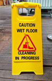 Caution wet floor sign cleaning in progress sign on wood floor.  Stock Image