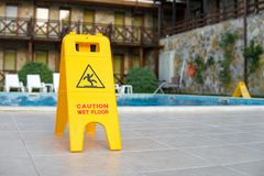 Caution wet floor sign near the swimming pool. Danger Stock Image