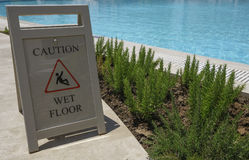 Caution wet floor sign on outdoor swimming pool. Royalty Free Stock Image